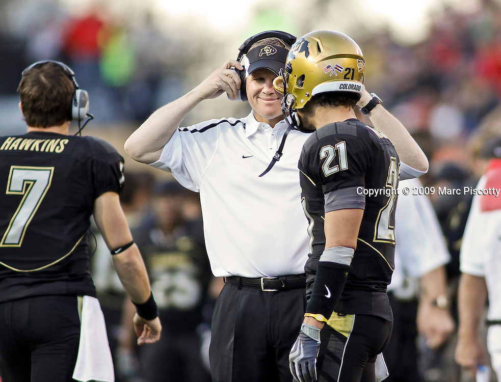 SHOT 11/27/09 4:49:02 PM - University of Colorado head football coach Dan Hawkins flashes a smile to Scotty McKnight (#21) as he works the sidelines against the Nebraska Cornhuskers during the second half of their game at Folsom Field in Boulder, Co. Hawkins' son Cody (#7) started at quarterback for the team earlier in the season. Hawkins has been under fire by fans and the media for failing to turn the underachieving program around. Nebraska won the game 28-20. (Photo by Marc Piscotty / © 2009)