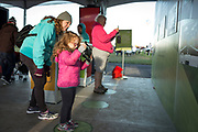Julianna Brumer gets a little help with an augmented reality game from AARP's Diana Kurnit at the AARP Block Party at the Albuquerque International Balloon Fiesta in Albuquerque New Mexico USA on Oct. 8th, 2018.