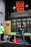 Activists scale the entrance to the Department For Work and Pensions, blocking it with people who were locked-on, on the 8th of February 2021, London, United Kingdom. An activist pretending to be from the National Eviction Team, cutting the lock-on with a saw and mistreating the protesters. The activists demanded to speak to the Health and Safety executive from the DWP to raise their concerns about the treatment of the activists in Euston Gardens who are currently underground in a tunnel in Euston Gardens, outside Euston Station to stop the building works related to the high speed train project HS2. The activists are concerned about the way the bailiffs and the National Eviction. The activists stopped their protest not to hold up ambulances which were called in by police for their safety. One activist was detained but soon after released and no arrest were made. All were given and accepted fines for breaching Covid-19 rules.