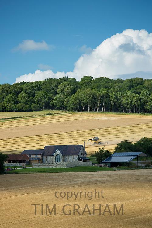 Combine harvester at work in a crop field on Salisbury Plain in Wiltshire, UK