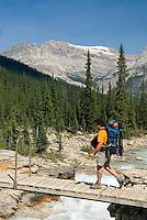 Backpacker crossing the bridge over Twin Falls Creek, Yoho National Park British Columbia Canada