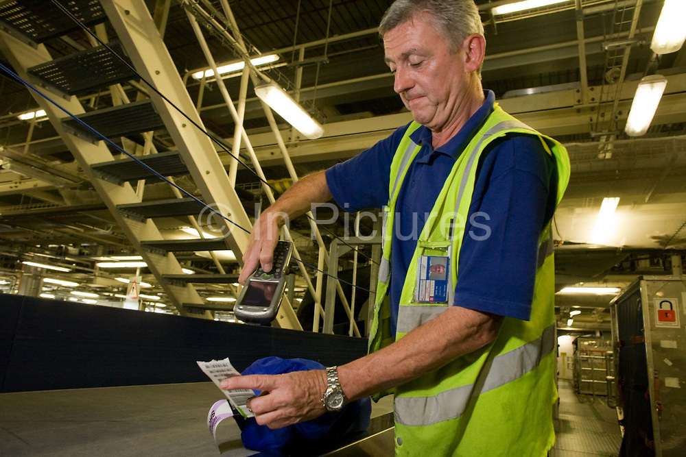 """A British Airways baggage handler scans the bar code of his airline passenger's item of luggage before loading it into the aircraft hold container bins. 50-70,000 pieces of BA baggage a day travel through 11 miles of conveyor belts which were installed in a 5-storey underground hall beneath the 400m (a quarter of a mile) length of Terminal 5 at Heathrow Airport. T5 alone has the capacity to serve around 30 million passengers a year and was completed in 2008 at a cost of £4.3bn. The system was designed by an integrated team from the airport operator BAA, BA and Vanderlande Industries of the Netherlands, and handles both intra-terminal and inter-terminal luggage. From writer Alain de Botton's book project """"A Week at the Airport: A Heathrow Diary"""" (2009)."""