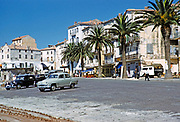 Calvi, Corsica, France in late 1950s cars parked in town with palm trees