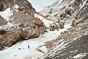 An opium dealer makes his way on slippery ground. In winter everything is frozen solid, including the young Amu Darya river. For most of the year, the only way to access the Afghan Pamir is by walking up this frozen river. The dangers are real, and people regularly die by falling through the ice or getting hit by avalanches...Between Kher Metek and Mirzo Murad shepherd house...Trekking down the Wakhan frozen river, the only way down to leave the high altitude Little Pamir plateau, home of the Afghan Kyrgyz community.