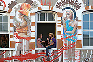 Couple chatting in the window of a muralled building on Long Street in Cape Town, South Africa.