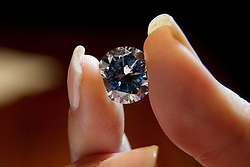 © Licensed to London News Pictures. 09/09/2013. London, UK. A Sotheby's employee holds 'The Premier Blue' a rare 7.59 carat flawless vivid blue diamond, which is estimated to achieve GB£12 million (US$19 million) at a press view held at the London based auction house's New Bond Street premises today (09/09/2013). The diamond, forming part of a sale of jewels and jadeite, is set to go on sale in Sotheby's Hong Kong on the 7th of October 2013. Photo credit: Matt Cetti-Roberts/LNP