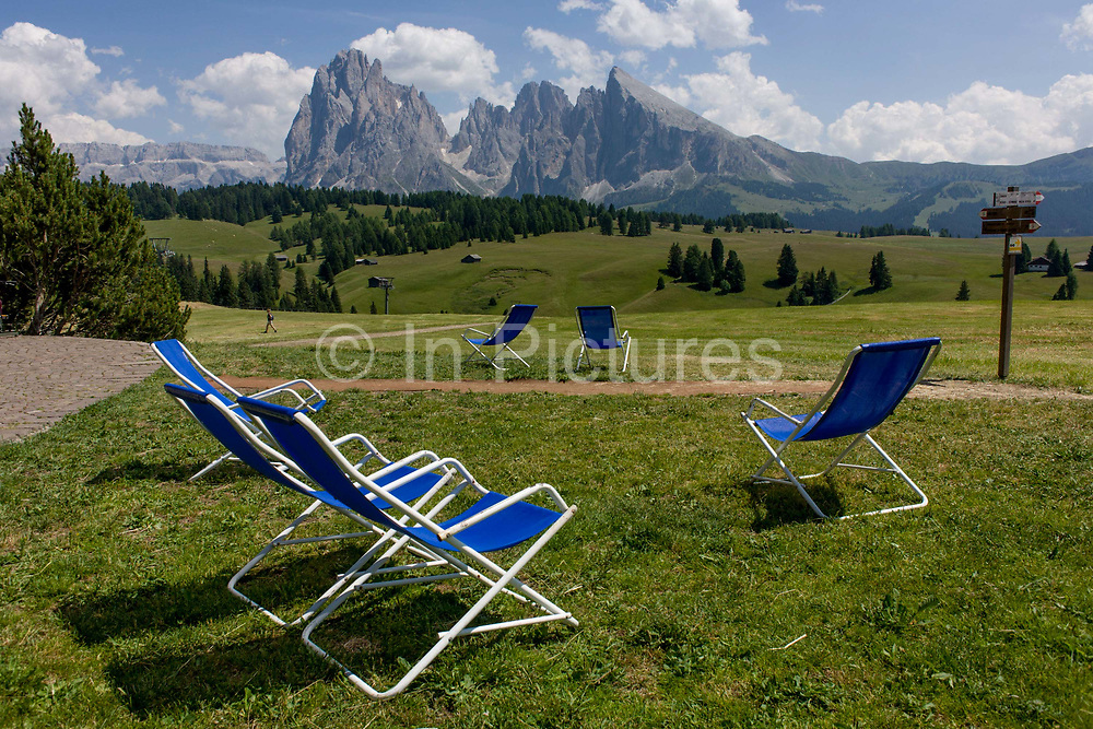 Sunbathing deckchairs for resting hikers on the Alpe di Siusi (German: Seiser Alm) plateau, above the South Tyrolean town of Ortisei-Sankt Ulrich in the Dolomites, Italy. Walking along one of the dozens of paths, hikers enjoy panoramic views of the peaks that envelope the location.  The Alpe di Siusi is the biggest high-alpine pasture in Europe with a surface of 57 km² and its altitude range from 1680 to 2350 m above sea level. This high-alpine pasture is located in the heart of the Dolomites surrounded by the Sasso Lungo Mountain Group, the Sciliar Nature Park, and the Catinaccio Mountain Group, the Northern Alps and the Sciliar Mountain Massif with Santner Peak.