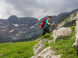 Woman hiking in the High Pyrenees view of cirque d'Estaube in background, Gavarnie, France