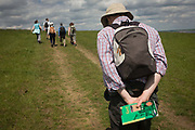 A group of country ramblers walk down a slope of grassland near Halstow on the Kent Thames estuary marshes, potentially threatened by the future London airport. With a guide to Kent walks, a man walks stooped while his friends walk ahead. With the panoramic views beyond, the landscape could controversially become the site for London's estuary airport, built on reclaimed and marshland on the river Thames, east of the city. Current London mayor Boris Johnson is in faviour of this project to alleviate pressure from other airport hubs, regardless of wildlife (especially a nearby protected bird sanctuary).