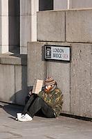 homeless man sits beneath london bridge sign