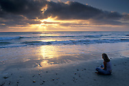 Young woman watches the sunset over the+Pacific from Torrey Pines State Beach, San Diego County, CALIFORNIA