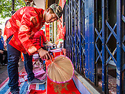 "04 FEBRUARY 2016 - BANGKOK, THAILAND: A worker dries freshly painted Chinese New Year calligraphy on a sidewalk in Bangkok's Chinatown district, before the celebration of the Lunar New Year. Chinese New Year, also called Lunar New Year or Tet (in Vietnamese communities) starts Monday February 8. The coming year will be the ""Year of the Monkey."" Thailand has the largest overseas Chinese population in the world; about 14 percent of Thais are of Chinese ancestry and some Chinese holidays, especially Chinese New Year, are widely celebrated in Thailand.      PHOTO BY JACK KURTZ"
