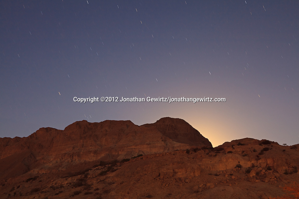 In the small hours of the night, the glow from the setting Moon is visible behind the hills of the Ein Gedi nature preserve near the Dead Sea. WATERMARKS WILL NOT APPEAR ON PRINTS OR LICENSED IMAGES.