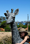 Child (6 years old) hugging statue of young giraffe. Taronga Zoo, Sydney, Australia