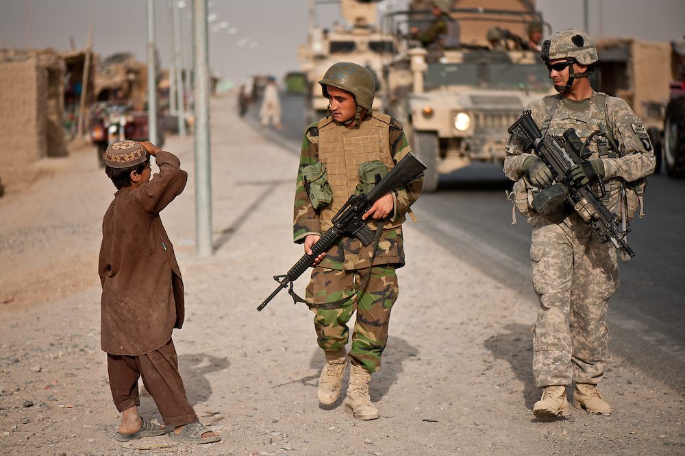 """An Afghan boy watches an American soldier and an Afghan soldier on patrol as part of a """"shonna b' shonna,"""" or shoulder-to-shoulder, training program."""