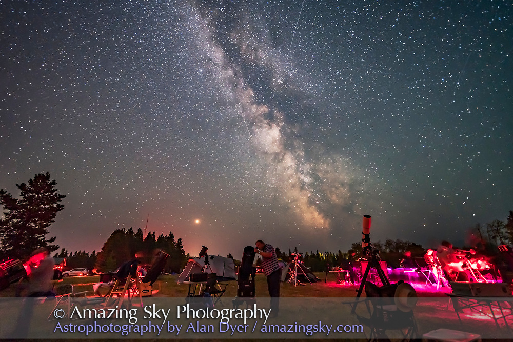 An observer gazes skyward with his Dobsonian reflector telescope at the Saskatchewan Summer Star Party on August 9, 2018, in the Cypress Hills of southwest Saskatchewan, at the Cypress Hills Interprovincial Park, a Dark Sky Preserve. The Milky Way shines to the south. Smoke in the sky obscures the horizon somewhat. <br /> <br /> About 350 stargazers attend the SSSP every year. <br /> <br /> This is a single 25-second exposure with the Loawa 15mm lens at f/2 and Sony a7III at ISO 3200.