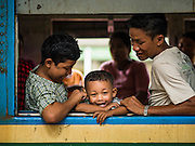 26 OCTOBER 2015 - YANGON, MYANMAR: A family on the Yangon Circular Train in the Yangon Central Station. The Yangon Circular Railway is the local commuter rail network that serves the Yangon metropolitan area. Operated by Myanmar Railways, the 45.9-kilometre (28.5mi) 39-station loop system connects satellite towns and suburban areas to the city. The railway has about 200 coaches, runs 20 times daily and sells 100,000 to 150,000 tickets daily. The loop, which takes about three hours to complete, is a popular for tourists to see a cross section of life in Yangon. The trains run from 3:45 am to 10:15 pm daily. The cost of a ticket for a distance of 15 miles is ten kyats (~nine US cents), and for over 15 miles is twenty kyats (~18 US cents).     PHOTO BY JACK KURTZ