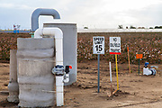 No oilfield traffic sign next to groundwater well with oil well pumpjack and cotton field in background. Kern County, located over the Monterey Shale, has seen a dramatic increase in oil drilling and hydraulic fracking in recent years. San Joachin Valley, California, USA