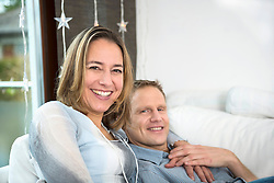 Happy couple sitting on sofa at home