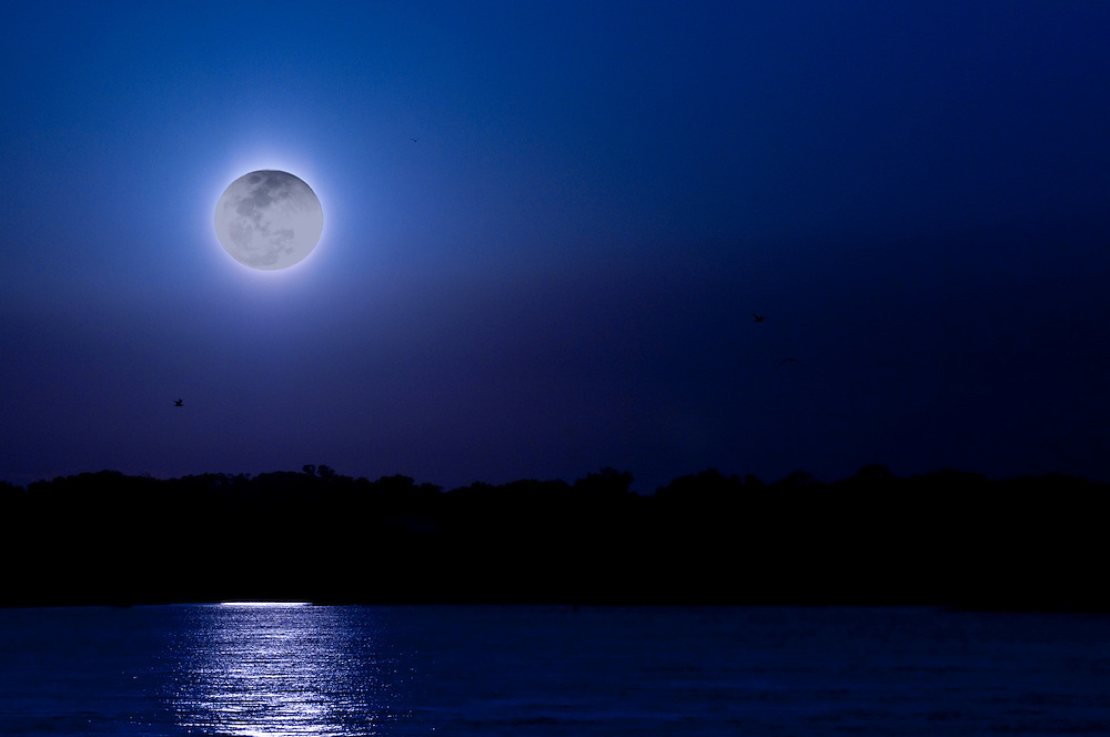 Moon reflections over the ocean at night.