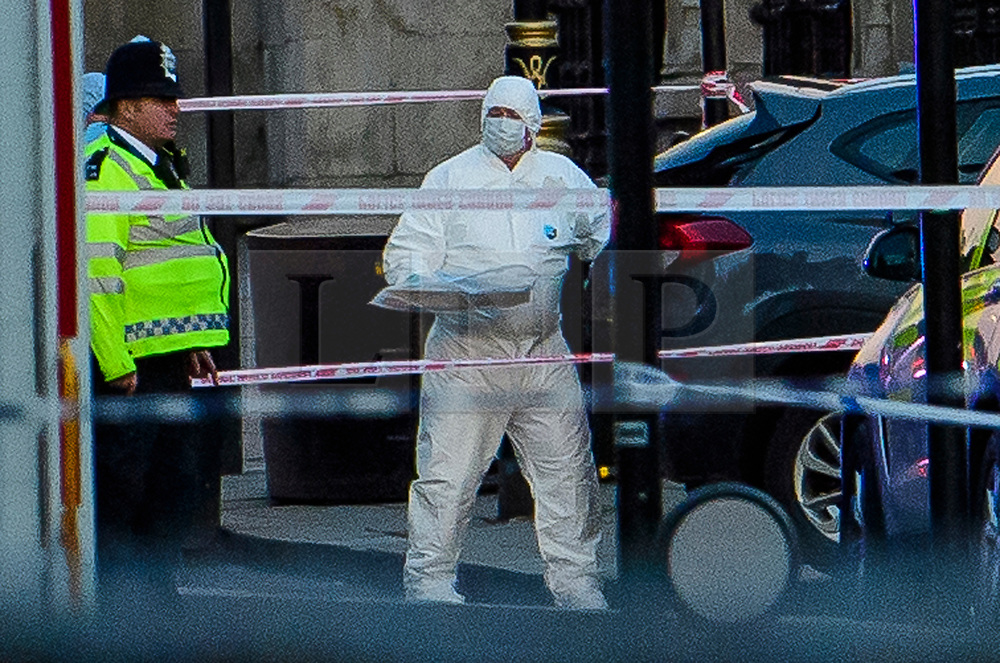 © Licensed to London News Pictures. 22/03/2017. London, UK. Police forensics carry evidence form the boot of a car (grey) involved in the incident, at the scene of suspected terrorist attack near Houses of Parliament in Westminster, London. Photo credit: Ben Cawthra/LNP