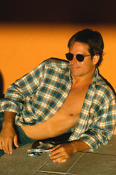 Man with an open shirt and sunglasses against a wall during a sunset