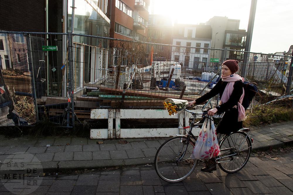 Een meisje fietst met bloemen langs het Ledig Erf in Utrecht