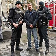 """Amsterdam, 17-04-2013. Op het Leidseplein te Amsterdam, voor hotel Americain, vonden opnames plaats van de KRO-misdaadserie Penoza III. Een aantal zwaarbewapende """"agenten"""" verrichtten een nogal spectaculaire arrestatie uit. Ook in Penoza III is de leidende rol weggelegd voor Carmen, gespeeld door Monic Hendrickx. Op de foto tussen de zwaarbewapende """"agenten"""" acteur Raymond Thiry."""