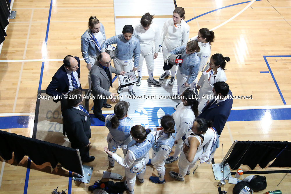 12 February 2017: Duke head coach Alex Beguinet (center, left) talks to his team after the match. The Duke University Blue Devils hosted the Boston College Eagles at Card Gym in Durham, North Carolina in a 2017 College Women's Fencing match. Duke won the dual match 19-8 overall, 6-3 Foil, 5-4 Epee, and 8-1 Saber.