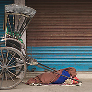 """A rickshaw puller sleaping next to his vehicle near 'New Market' in Kolkata...The hand-pulled rickshaw of Calcutta, immortalised by Dominic Lapierre's famous novel, City of Joy, will soon be a part of the history books as a bill passed by the West Bengal state assembly described the centuries-old mode of transport as """"inhumane."""".The future of about 18,000 rickshaw pullers in the city, earning an avarage daily wages of about 100 rupees ($2.5).is unclear as they call for a compensation package to help them rehabilitate into alternative jobs."""