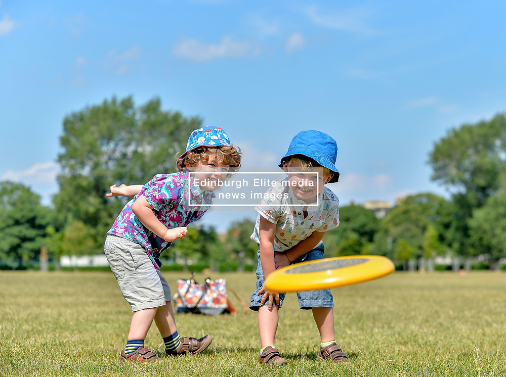 Pictured: 3 year old twins Corin and Elliott Brennan from Leith have fun in the sun playing frisbee on Leith Links as the Capital sweltered in 27 degree heat.<br /> <br /> © Dave Johnston / EEm
