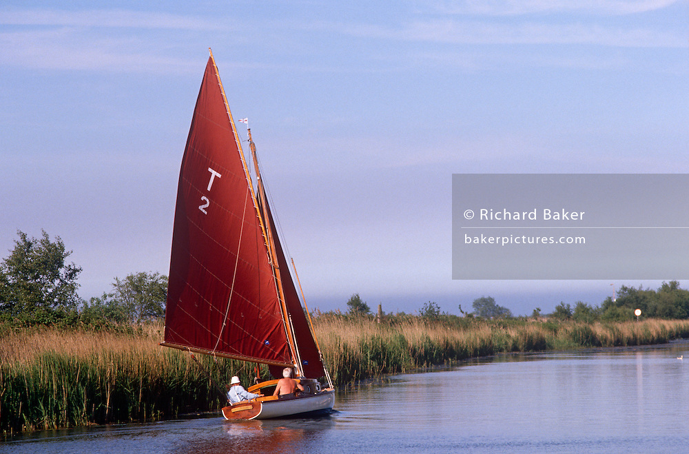 An elderly-looking couple sail away into the distance on the Norfolk Broads at Potter Heigham, Norfolk, England. With a large red sail hoisted on a slow breeze, the sailors progress at a sedate pace past reed beds in one of the National Nature Reserves (NNR) designated by Natural England as key places for wildlife and natural features in England. The Broads are a network of mostly navigable rivers and lakes in the English counties of Norfolk and Suffolk. The total area is 303 square kilometres (117 sq mi), most of which is in Norfolk, with over 200 kilometres (120 mi) of navigable waterways. There are seven rivers and 63 broads, mostly less than 4 metres (13 ft) deep. Thirteen broads are generally open to navigation, with a further three having navigable channels.