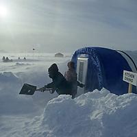 ANTARCTICA, Camp staffer shovels drifting snow during wind storm, Patriot Hills expedion base, Ellsworth Mts. (80 degrees south latitude).