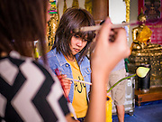 """12 OCTOBER 2012 - RAI KHRING, NAKHON PATHOM, THAILAND:   Thai Buddhists light candles to make merit at Wat Rai Khring in Nakhon Pathom province.  Wat Rai Khring was built in 1791. The Abbot at the time, Somdej Phra Phuttha Chan (Pook), named the temple after the district. When construction was completed, the Buddha image was brought from another temple and enshrined here. Later locals named the image """"Luang Pho Wat Rai Khing"""". The Buddha image is of Chiang Saen style and is assumed to have been built by Lanna Thai and Lan Chang craftsmen.    PHOTO BY JACK KURTZ"""