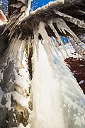 Frozen waterfall and icicles growing from fallen trees next to it on sunny winter day, Gauja National Park (Gaujas Nacionālais parks), Latvia Ⓒ Davis Ulands | davisulands.com
