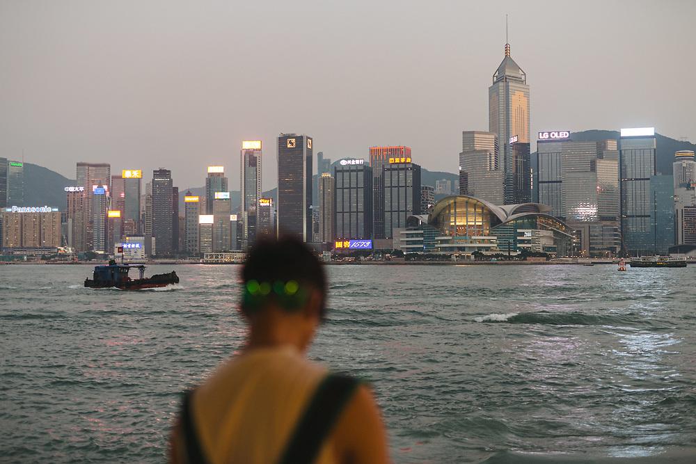 A man looks over the Victoria Harbor at the Hong Kong Island skyline, from Kowloon Public Pier along the Tsim Sha Tsui waterfront, in Tsim Sha Tsui, Kowloon, Hong Kong, China, on September 25, 2019.