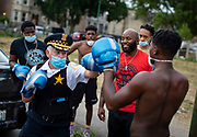 Chicago police Cmdr. Gil Calderon gets instructions from Derek Brown (in red) of Boxing Out Negativity while sparring with Brown's son, Derek Brown Jr., 16, during a peace gathering community event Wednesday, July 8, 2020 in North Lawndale. (Brian Cassella/Chicago Tribune)