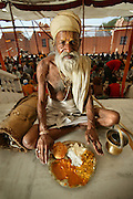 """Sitarani Tyaagi, an ascetic Hindu priest, with his typical day's worth of food at an ashram in Ujjain, India. (From the book What I Eat; Around the World in 80  Diets.)  The caloric value of his typical day's worth of food in the month of April was 1000 kcals. He is 70 years of age; 5 feet, 6 inches tall; and 103 pounds. Sitarani Tyaagi is one of thousands of ascetic Hindu priests?called Sadhus?that walk the country of India and receive food from observant Hindus. Generally, he eats one meal per day and has water for the other two meals. He has a small pot that he carries with him for water. Offer him more food than a plateful, and he will kindly say, """"no thanks.""""  MODEL RELEASED."""