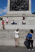 Young tourists play on the plinth of Nelsons Column in Trafalgar Square, on 10th August 2017, in London, England.