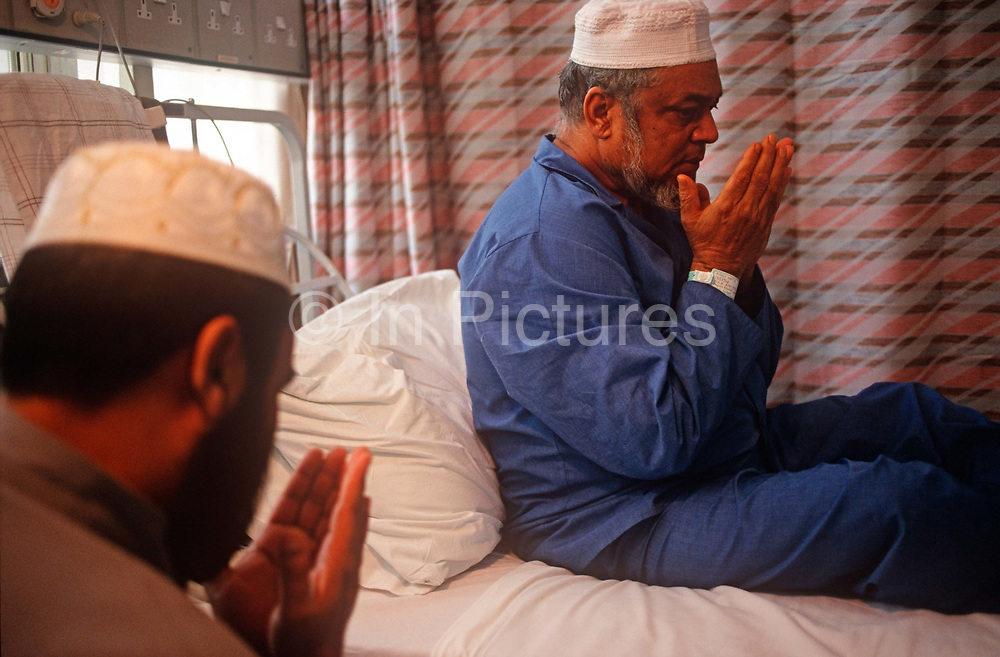 A recuperating Muslim community Imam prays at the bedside of a patient who is staying on the Phyllis Friend surgical ward, Royal London Hospital, on 23rd June 1993, in Whitechapel, London England. The Royal London is one of Londons oldest hospitals, having been founded in 1740 and is a major teaching hospital in Whitechapel, East London. It is part of the Barts and the London NHS Trust, alongside St Bartholomews Hospital Barts, which is a couple of miles away. Because of the cultural profile of East London, patients tend to be from many faiths, speaking many languages.