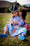 Laos, Muang Sing. Hmong girls in beautiful dresses sitting on the grass.