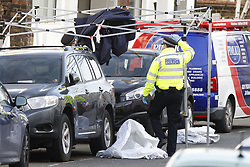 © Licensed to London News Pictures. 12/02/2021. London, UK. Police remove an evidence tent that had blown over at the crime scene in Parsons Green where a man, believed to be aged 19, died from stab injuries. Police were called at 18:42GMT on Thursday 11th February to reports of a fight between three people in Ackmar Road, the victim was pronounced dead at the scene. A second man, also believed to be in his late teens, with stab injuries was taken to hospital. His condition is not believed to be life-threatening. The third male had left the scene before police arrived. Photo credit: Peter Macdiarmid/LNP