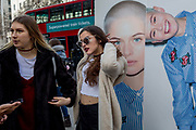 Models stand next to a street billboard for high-street retailer New Look, outisde London Fashion Week in the Strand, on 17th Febriary 2017, in London, England, United Kingdom. London Fashion Week is a clothing trade show held in London twice each year, in February and September. It is one of the Big Four fashion weeks, along with the New York, Milan and Paris. The fashion sector plays a significant role in the UK economy with London Fashion Week alone estimated to rake in £269 million each season. The six-day industry event allows designers to show their collections to buyers, journalists and celebrities and also maintains the city's status as a top fashion capital.