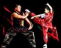 wushu chinese boxing kung fu Hung Gar fighter isolated child and man isolated on black background with speed light painting effect motion blur