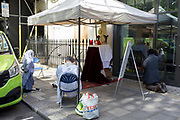 The UK government has imposed Coronavirus pandemic lockdown rules on religious gatherings so a priest accompanies two of his parishioners praying at a makeshift altar on the pavement outside St. Patrick's Catholic church in Soho Square, between construction work and some offices, on 22nd June 2020, in London, England. The government is expected soon to relax the social distance rules from two metres to one metre in a bid to restart the economy. However, in the last 24hrs a further 15 have died from Covid, bringing the total today to 42,647.