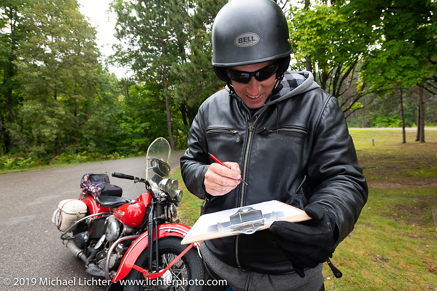 Canadian John Phillips got off his 1947 Harley-Davidson EL Knucklehead to answer the daily checkpoint pop quiz during the Cross Country Chase motorcycle endurance run from Sault Sainte Marie, MI to Key West, FL. (for vintage bikes from 1930-1948). Stage 1 from Sault Sainte Marie to Ludington, MI USA. Friday, September 6, 2019. Photography ©2019 Michael Lichter.