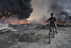October 21, 2016 - Qayyarah, Iraqi-Kurdistan, Iraq - A young boy sits on his bicycle amongst during oil wells in the town of Qayyarah, Iraq. The oil wells, located in a residential neighbourhood on the edge of the town, were part of a large oilfield set on firet in July by retreating Islamic State militants as part of a scorched earth policy. Since being retaken from the Islamic State the town of Qayyarah has become an important staging post for the Iraqi Army, and some US support elements, in the buildup to the Mosul offensive. (Credit Image: © Matt Cetti-Roberts/London News Pictures via ZUMA Wire)