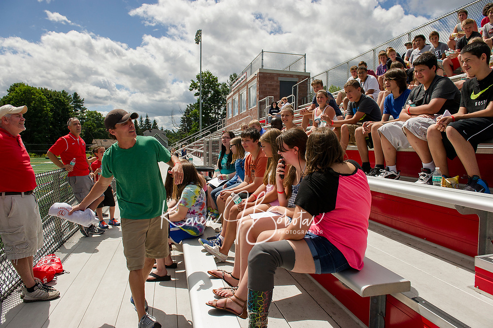 Asst Principal David Bartlett throws out a sweatshirt to a student with the correct answer to questions posed by Principal Jim McCullom during LHS Freshman orientation on Thursday morning.  (Karen Bobotas/for the Laconia Daily Sun)