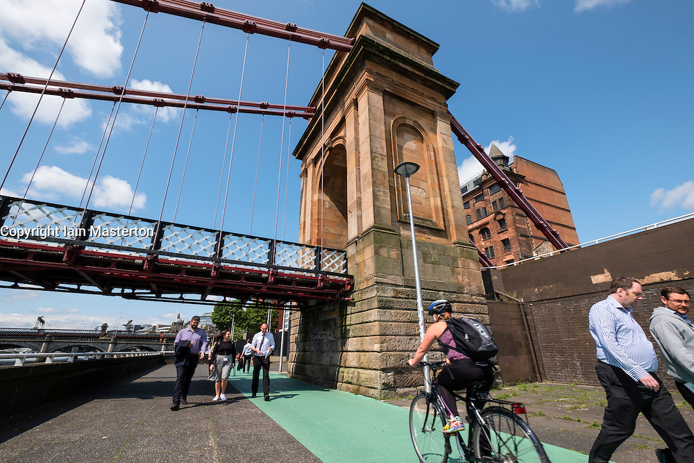 Cycleway and pedestrian walkway beneath Portland Street suspension bridge across the River Clyde in Glasgow, Scotland, United Kingdom