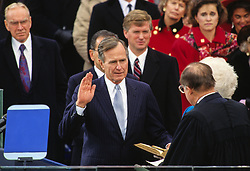 United States President George H.W. Bush is sworn-in as 41st President of the United States by Chief Justice William Rehnquist at the US Capitol on January 20, 1989. The Speaker of the US House of Representatives Jim Wright (Democrat of Texas) looks on from the left and US Vice President Dan Quayle looks on from the center. Photo by Arnie Sachs / CNP /ABACAPRESS.COM